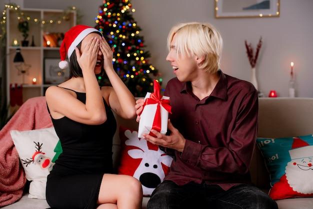 Blij jong paar thuis in kerstmistijd die santahoed draagt en giften ontvangt