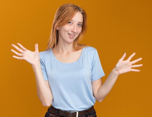 Blij jong roodharig gembermeisje met sproeten die handen open houden geïsoleerd op een oranje muur met kopieerruimte