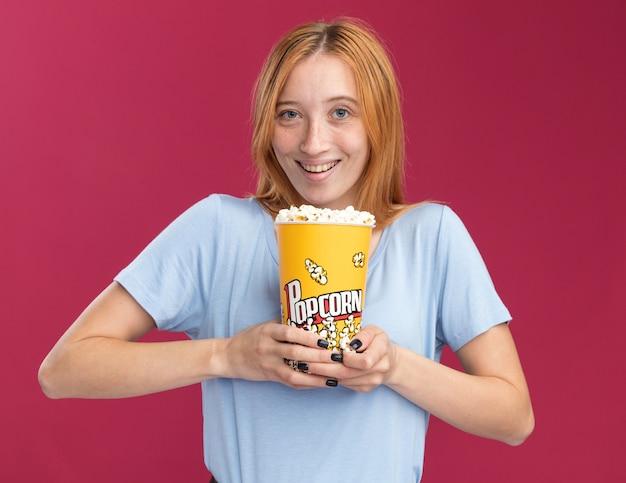 Blij jong roodharig gembermeisje met sproeten die popcornemmer houden die op roze muur met exemplaarruimte wordt geïsoleerd