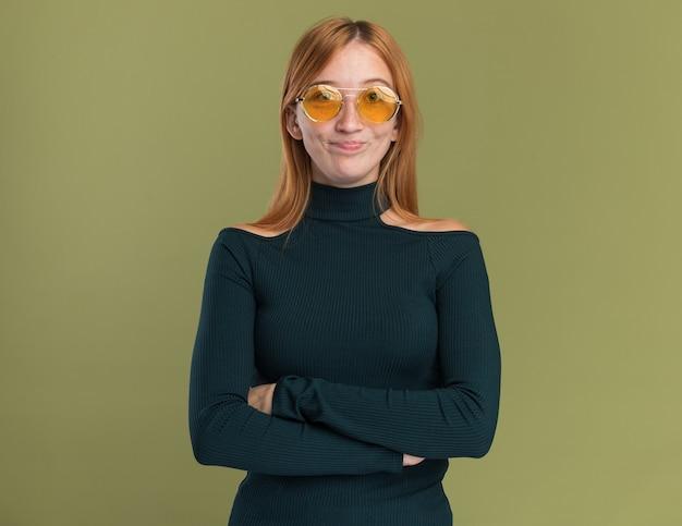 Blij jong roodharig gembermeisje met sproeten in zonnebril die zich met gekruiste wapens op olijfgroen bevinden