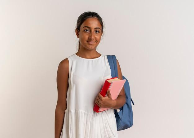 Blij jong schoolmeisje die achterzak met boek met notitieboekje op wit dragen