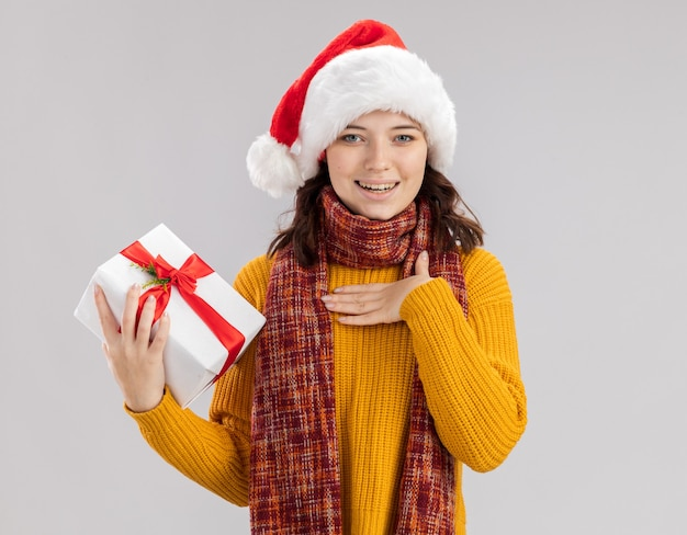 Blij jong slavisch meisje met kerstmuts en met sjaal om de nek legt hand op de borst en houdt kerst geschenkdoos geïsoleerd op een witte achtergrond met kopie ruimte