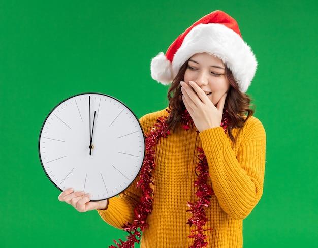 Blij jong slavisch meisje met kerstmuts en met slinger om nek legt hand op mond houden en kijken naar klok geïsoleerd op groene achtergrond met kopie ruimte