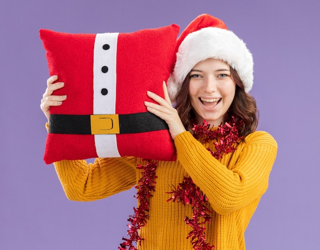 Blij jong slavisch meisje met kerstmuts en met slinger om nek met versierd kussen geïsoleerd op paarse achtergrond met kopie ruimte