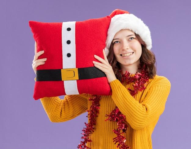 Blij jong slavisch meisje met kerstmuts en met slinger om nek met versierd kussen opzoeken geïsoleerd op paarse achtergrond met kopie ruimte