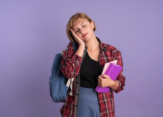 Blij jong slavisch studentenmeisje met rugzak legt hand op gezicht houdt boek en notitieboekje vast