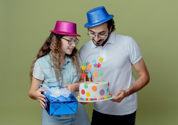 Blij jong stel dat roze en blauwe de giftdoos van de hoedenmeisje houdt en kerel die en met meisje op verjaardagstaart houdt kijkt