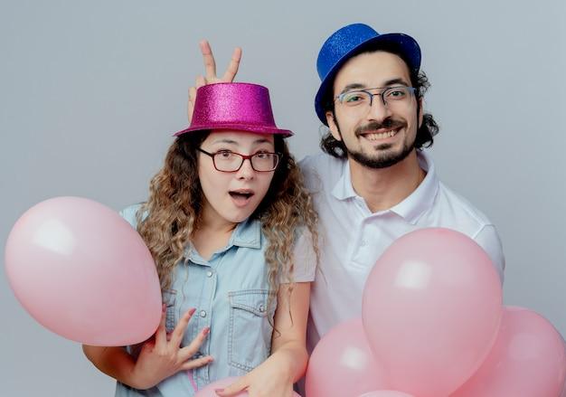 Blij jong stel dat roze en blauwe hoedenkerel draagt die het gebaar van konijntjesoren aan de ballons van de meisjesholding op witte achtergrond wordt geïsoleerd