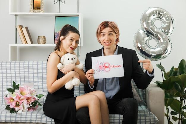 Blij jong stel op gelukkige vrouwendag met teddybeer en wenskaart zittend op de bank in de woonkamer
