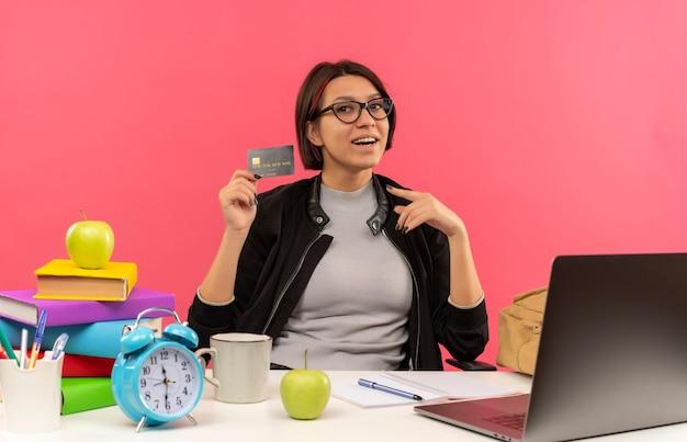 Blij jong studentenmeisje die glazen dragen die bij bureau houden en op creditcard houden die huiswerk doen dat op roze wordt geïsoleerd