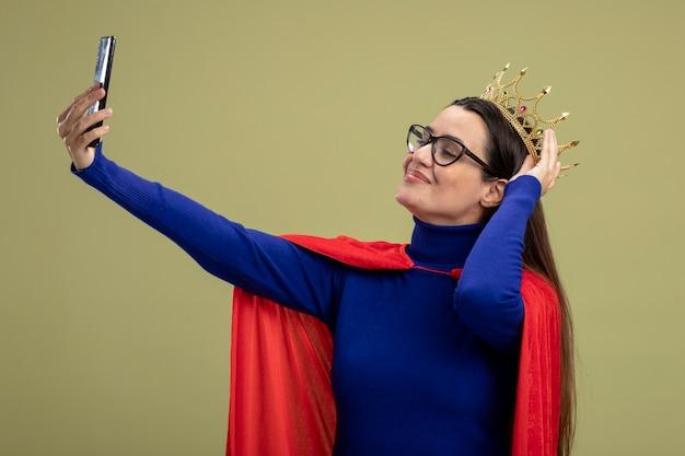 Blij jong superheld meisje bril zetten kroon op hoofd en neem een selfie geïsoleerd op olijfgroene achtergrond