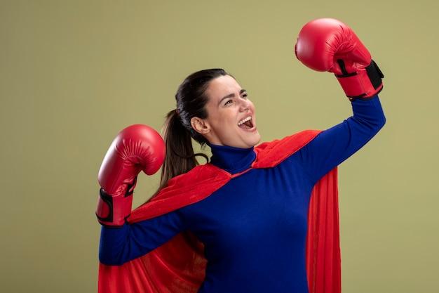 Blij jong superheldenmeisje die kant bekijken die bokshandschoenen dragen die sterk gebaar tonen dat op olijfgroen wordt geïsoleerd
