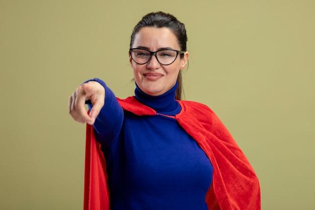Blij jong superheldmeisje dat een bril draagt die u gebaar toont dat op olijfgroene achtergrond wordt geïsoleerd