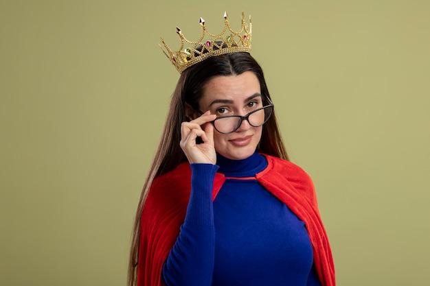 Blij jong superheldmeisje dat kroon draagt en een bril draagt en grijpt die op olijfgroene achtergrond wordt geïsoleerd
