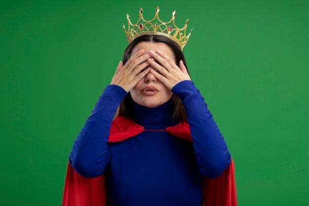 Blij jong superheldmeisje die kroon behandelde ogen met handen dragen die op groen worden geïsoleerd