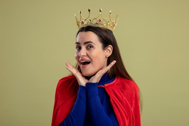 Blij jong superheldmeisje die kroon dragen die handen op wangen zetten die op olijfgroene achtergrond worden geïsoleerd
