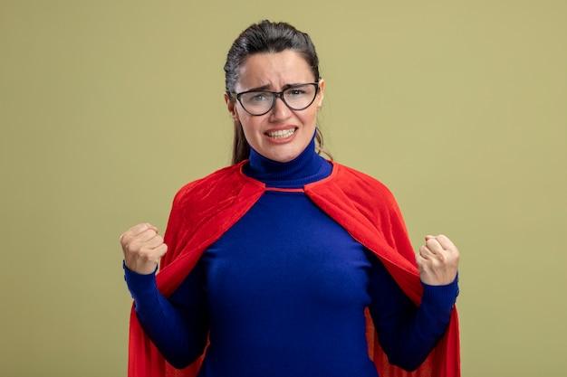 Blij jong superheromeisje die glazen dragen die ja gebaar tonen dat op olijfgroene achtergrond wordt geïsoleerd