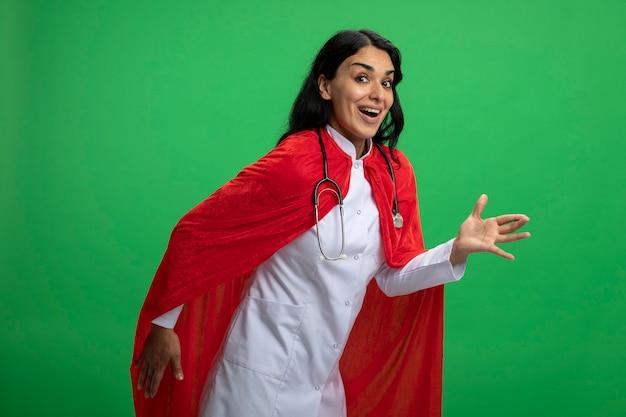 Blij jong superheromeisje die medisch kleed met stethoscoop dragen die robotstijl tonen die op groen wordt geïsoleerd