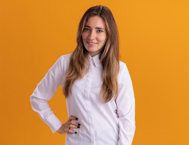 Blij jong, vrij blank meisje legt hand op taille geïsoleerd op oranje muur met kopieerruimte