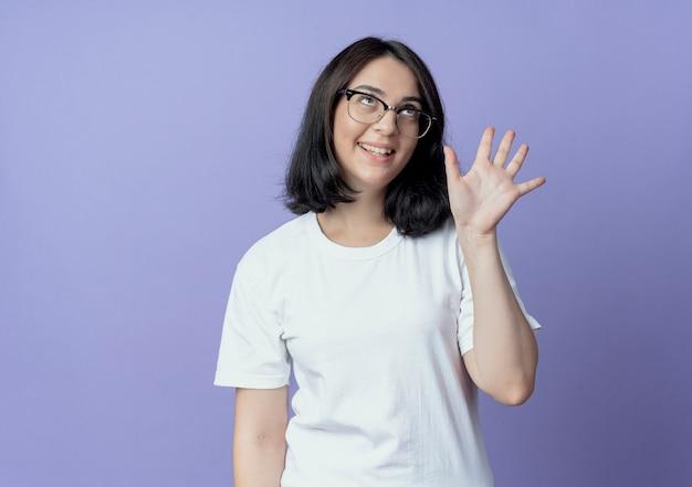 Blij jong vrij kaukasisch meisje dat een bril draagt en vijf met hand toont die op purpere achtergrond met exemplaarruimte wordt geïsoleerd