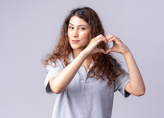 Blij jong vrij kaukasisch meisje dat hartteken doet dat op witte muur wordt geïsoleerd