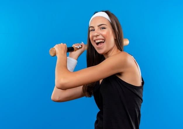 Blij jong vrij sportief meisje die hoofdband en polsbandje dragen die honkbalknuppel houden die op blauwe ruimte wordt geïsoleerd