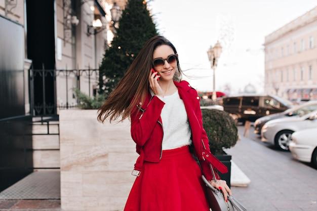 Blij jong wit vrouwelijk model in rode kleding die op telefoon spreekt