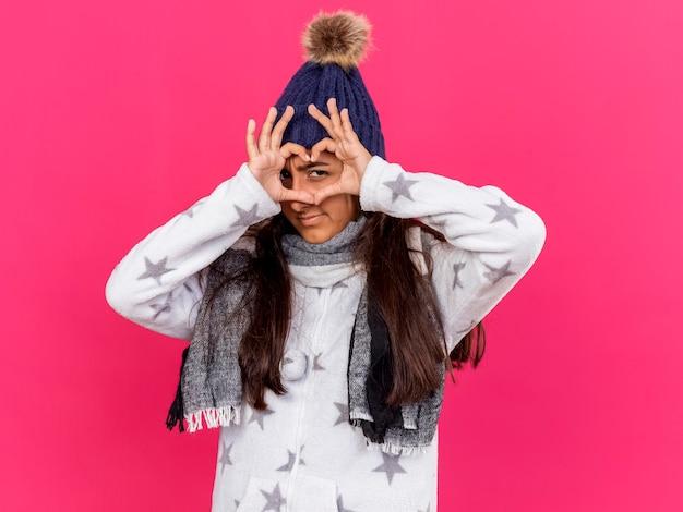 Blij jong ziek meisje dat de winterhoed met sjaal draagt die hartgebaar toont dat op roze achtergrond wordt geïsoleerd