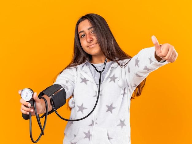 Blij jong ziek meisje dat haar eigen druk meet met bloeddrukmeter die duim toont die omhoog op gele achtergrond wordt geïsoleerd