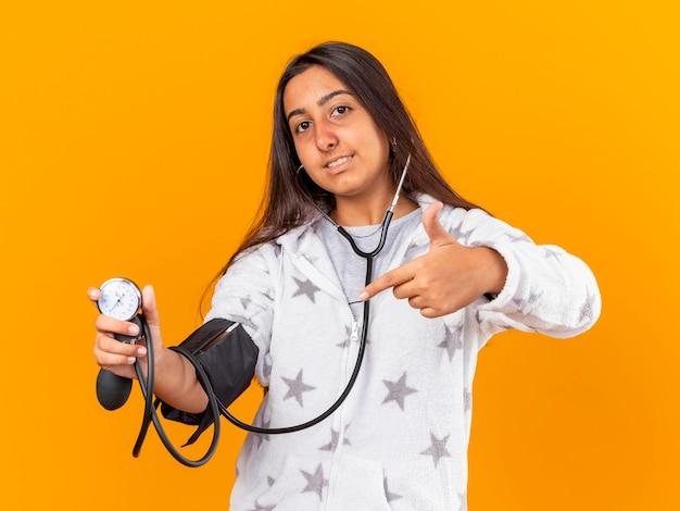 Blij jong ziek meisje dat haar eigen druk meet met bloeddrukmeter die op geel wordt geïsoleerd