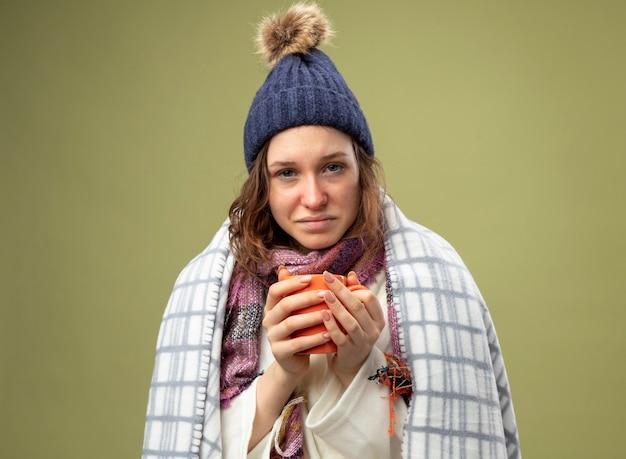 Blij jong ziek meisje dragen witte mantel en winter hoed met sjaal verpakt in plaid houden kopje thee geïsoleerd op olijfgroen