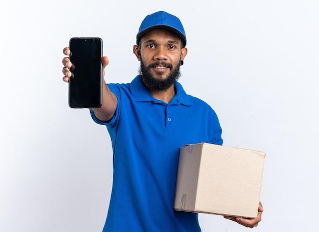 Blij jonge afro-amerikaanse bezorger met kartonnen doos en telefoon geïsoleerd op een witte achtergrond met kopie ruimte