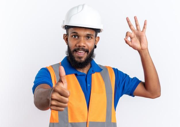 Blij jonge afro-amerikaanse bouwer man in uniform met veiligheidshelm duimen omhoog en gebaren ok teken geïsoleerd op een witte achtergrond met kopie ruimte