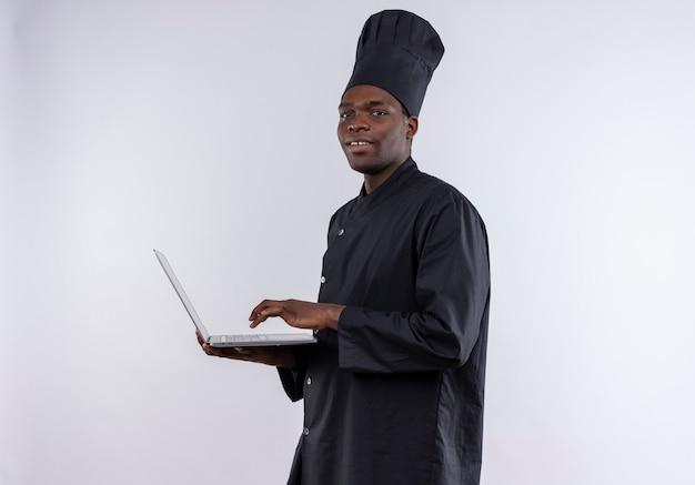Blij jonge afro-amerikaanse kok in uniform chef houdt laptop en kijkt naar de camera op wit met kopie ruimte