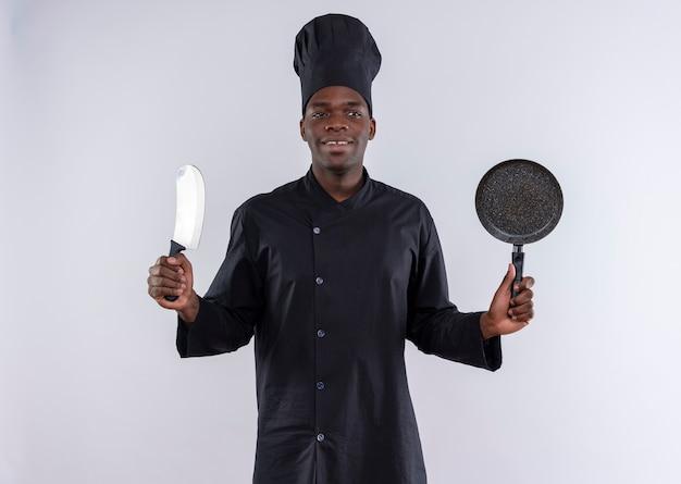 Blij jonge afro-amerikaanse kok in uniform chef houdt mes en koekenpan kant op wit met kopie ruimte kijken