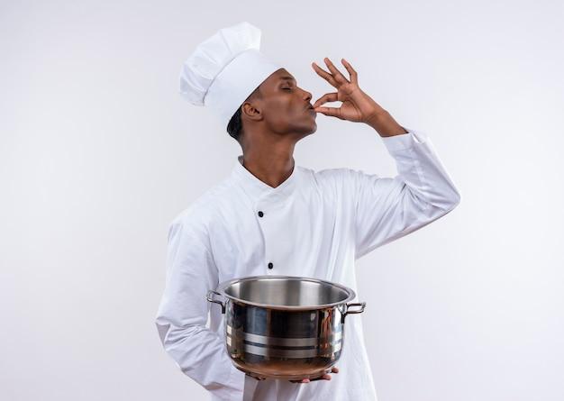 Blij jonge afro-amerikaanse kok in uniform chef houdt steelpan en gebaren lekker heerlijk met hand op geïsoleerde witte achtergrond met kopie ruimte