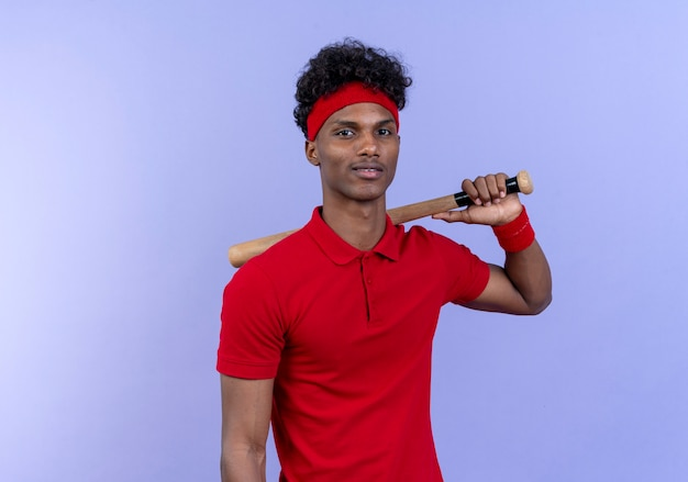 Blij jonge afro-amerikaanse sportieve man met hoofdband en polsband houdt het bit op de schouder geïsoleerd op blauwe muur
