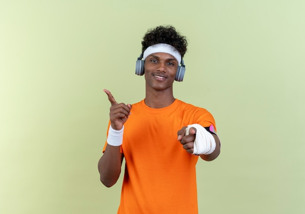 Blij jonge afro-amerikaanse sportieve man met hoofdband en polsbandje en telefoonarmband met koptelefoon toont je gebaar en punten aan de zijkant geïsoleerd op groene achtergrond met kopie ruimte