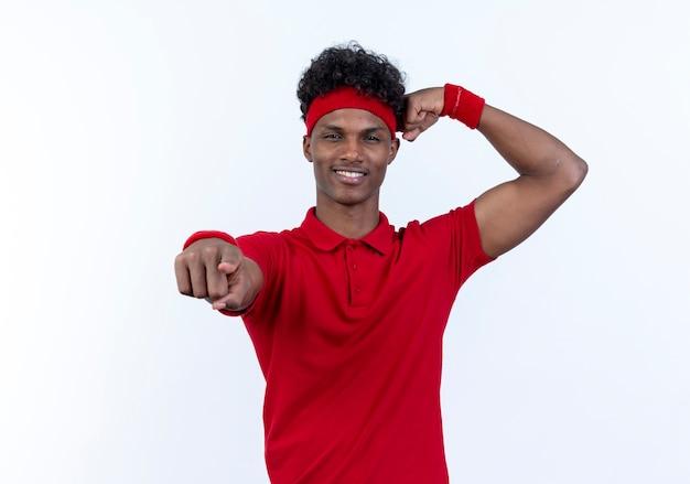 Blij jonge afro-amerikaanse sportieve man met hoofdband en polsbandje toont je gebaar en doet sterk gebaar geïsoleerd op een witte achtergrond