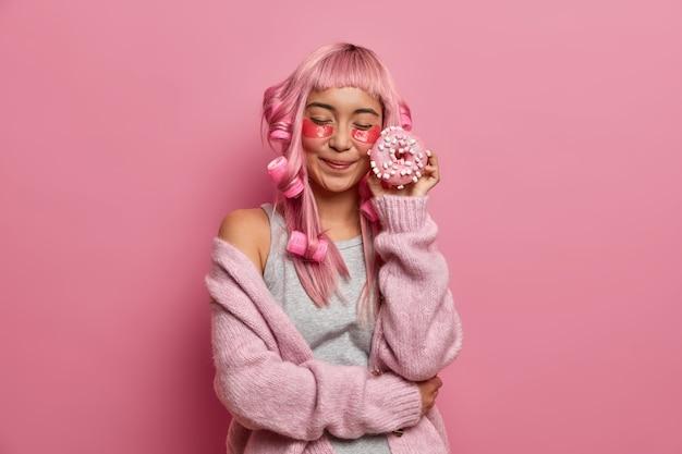 Blij jonge aziatische vrouw met roze haar, ogen sluit houdt heerlijke donuts in de buurt van gezicht, collageen patches onder ogen toepast, krullend kapsel maakt