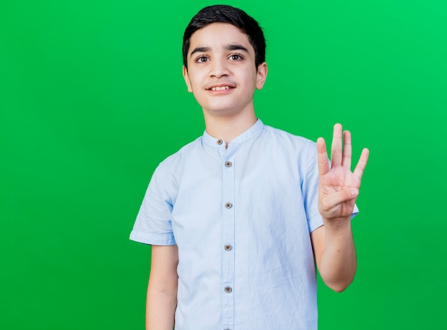 Blij jonge blanke jongen kijken naar camera met vier met hand geïsoleerd op groene achtergrond met kopie ruimte