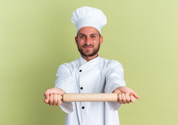 Blij jonge blanke mannelijke kok in chef-kok uniform en pet kijken camera uitrekken deegroller naar camera geïsoleerd op olijfgroene muur