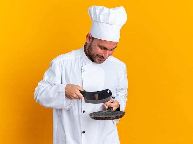 Blij jonge blanke mannelijke kok in chef-kok uniform en pet met koekenpan en hakmes erboven kijkend naar koekenpan geïsoleerd op oranje muur met kopieerruimte