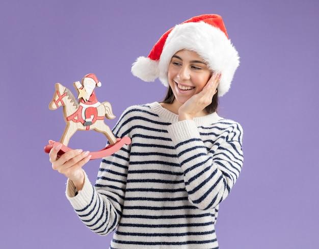 Blij jonge blanke meisje met kerstmuts legt hand op gezicht houden en kijken naar santa op schommelpaard decoratie geïsoleerd op paarse muur met kopie ruimte