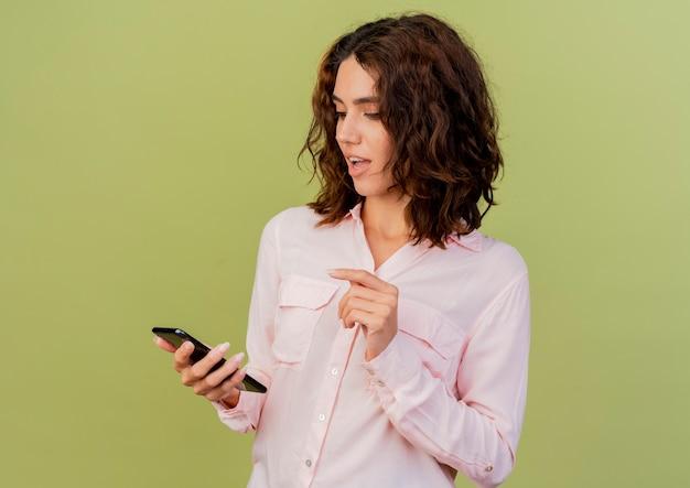 Blij jonge blanke vrouw houdt en kijkt naar telefoon geïsoleerd op groene achtergrond met kopie ruimte