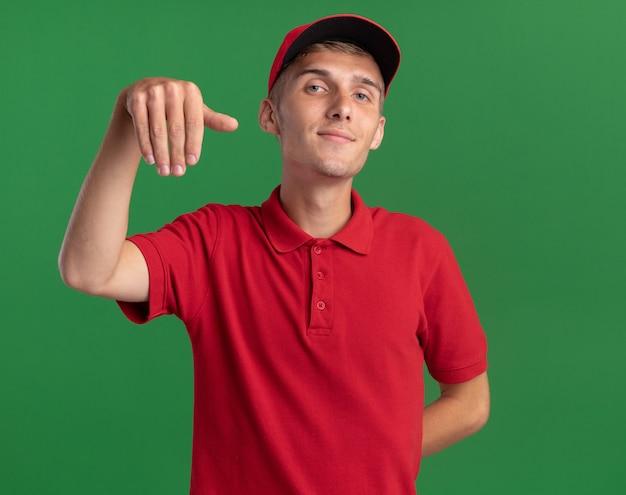Blij jonge blonde bezorger houdt hand ondersteboven geïsoleerd op groene muur met kopieerruimte