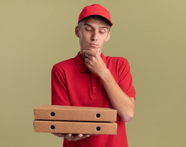 Blij jonge blonde bezorger legt hand op kin houden en kijken naar pizzadozen op olijfgroen