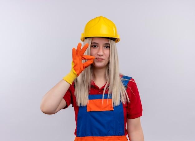 Blij jonge blonde ingenieur bouwer meisje in uniform dragen handschoenen doen ok teken op geïsoleerde witte ruimte met kopie ruimte