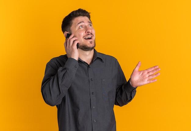 Blij jonge blonde knappe man praten aan de telefoon kijken naar kant geïsoleerd op oranje muur