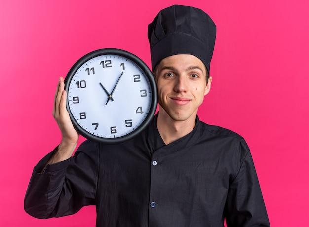 Blij jonge blonde mannelijke kok in chef-kok uniform en pet met klok aanraken gezicht met het kijken naar camera geïsoleerd op roze muur